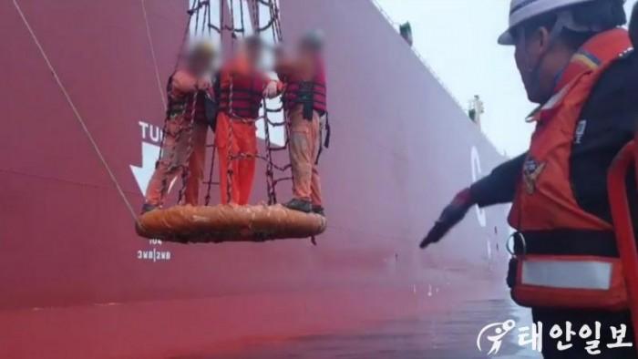 해양경찰 단정으로 옮겨태우기 위해 응급환자를 대형상선 크레인줄에 달아 내리고 있다.jpg
